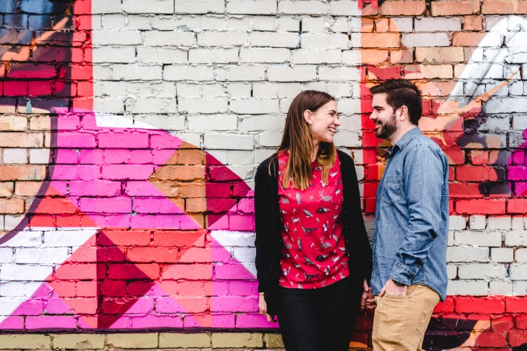 Engaged couple standing next to a grafiti wall
