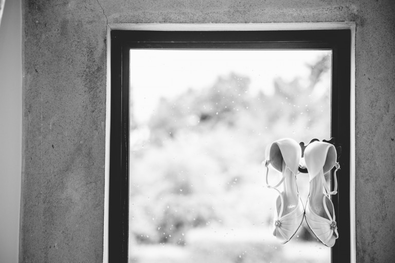 brides shoes hanging in a window