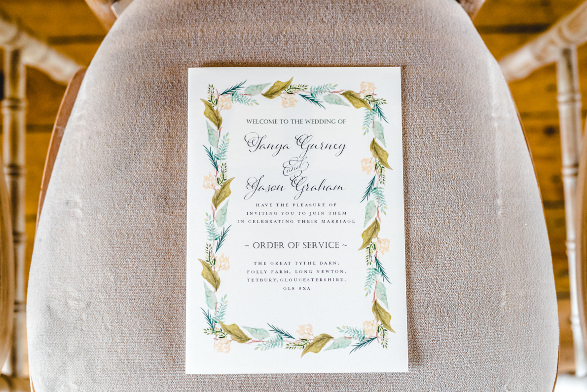great tythe barn wedding order of service on a chair
