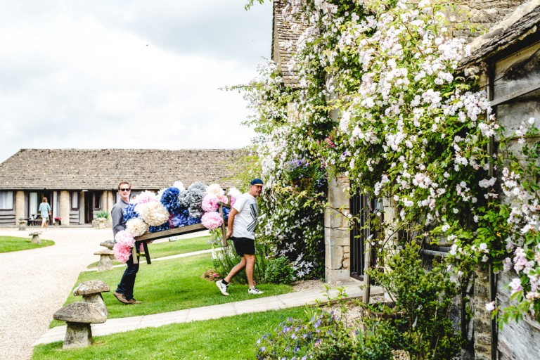 helpers carrying a bench full of pom poms at the great tythe barn tetbury