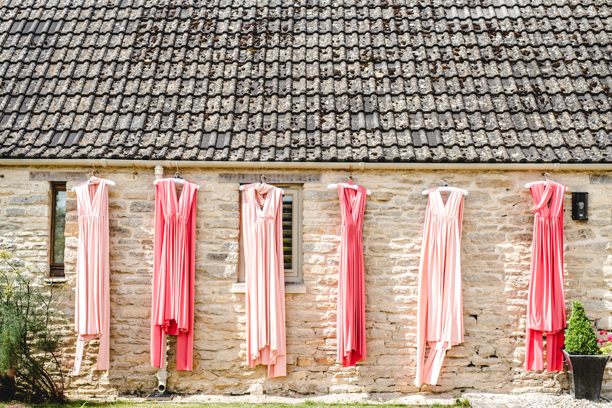 six pink bridesmaids dresses hanging outside