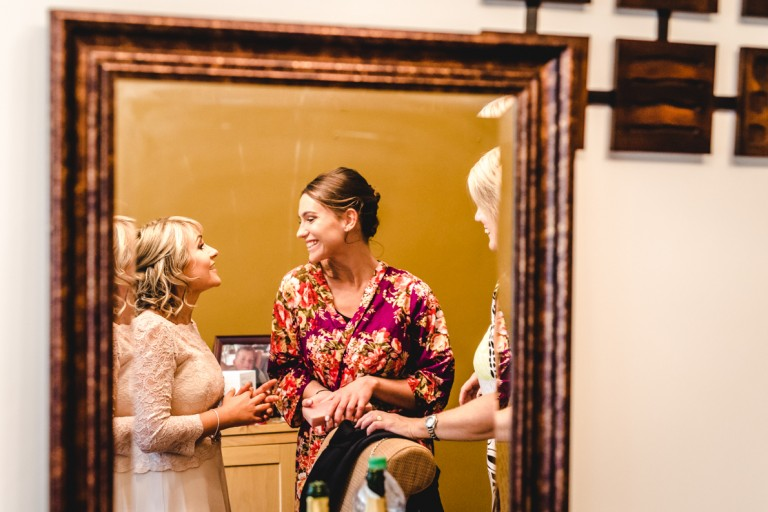 bride and her bestie reflected in a mirror