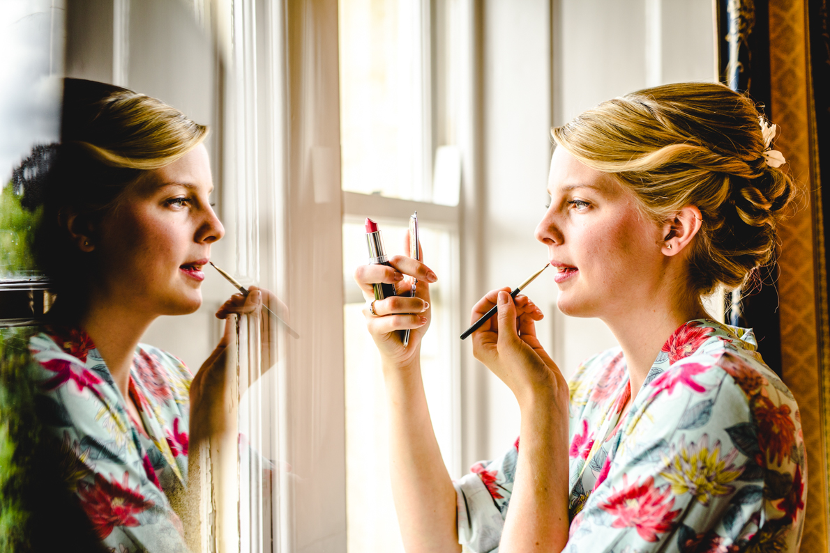 A bride applying make-up on her wedding day