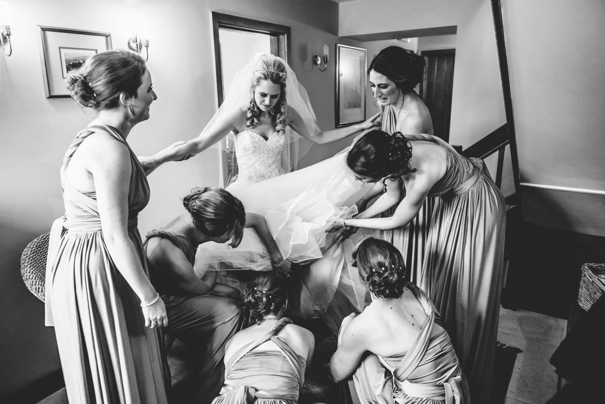 Six bridesmaids fitting a bride into her wedding dress