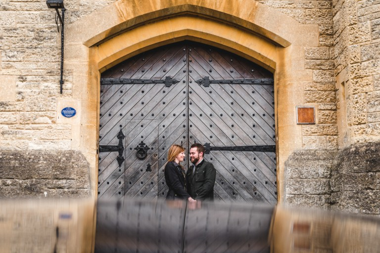 engaged couple standing in front of a door in Cirencester