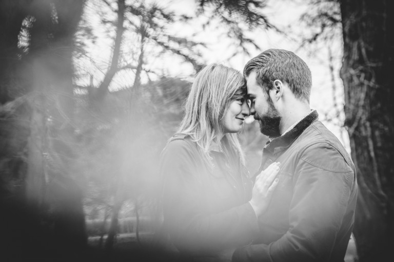 Black and white engagement photo of a couple with their heads together
