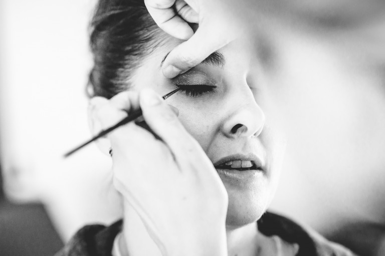 A close up of a bride having make-up applied