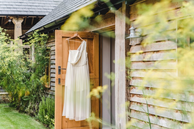 A brides dress hanging on a doorway at the barn at upcote