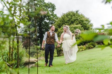Bride and groom walking in the garden at The Barn at Upcote