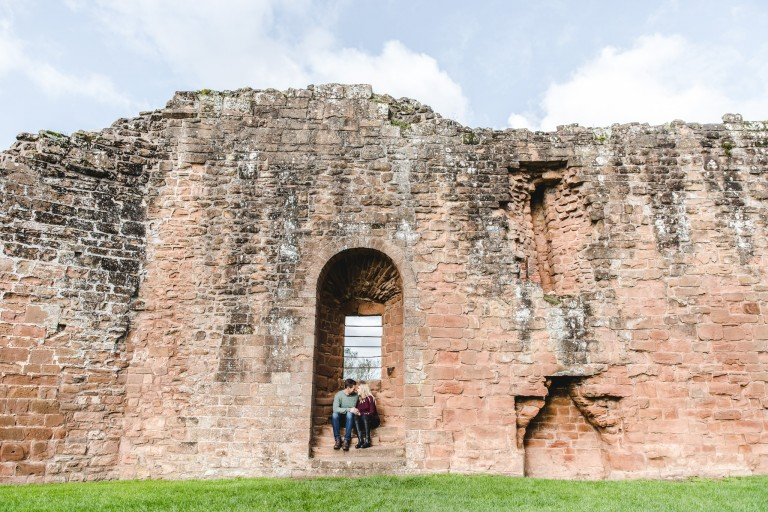 A wide view of a couple sat in an alcove at Kenilworth Castle