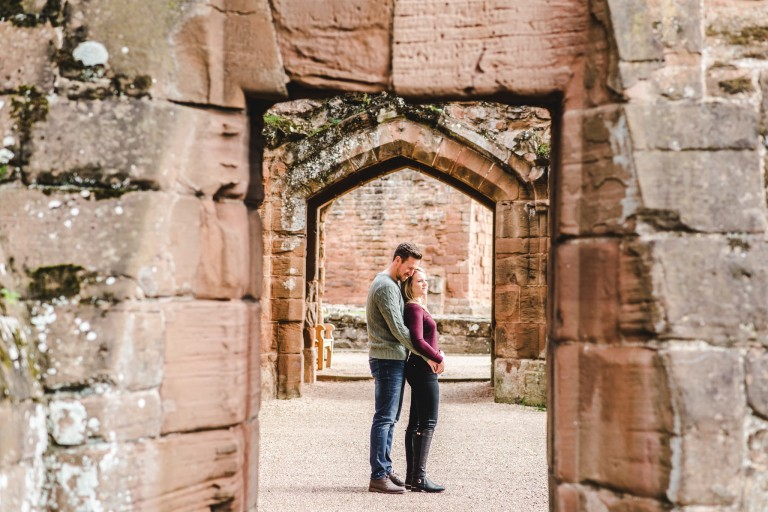 An engaged couple stood in a doorway at Kenilworth Castle