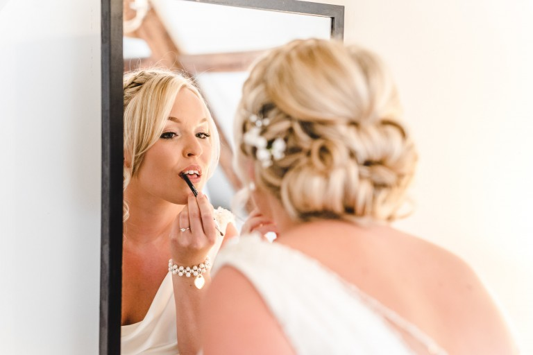A bride applying lipstick