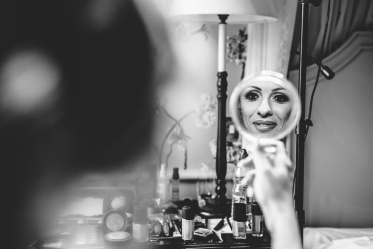 A made-up brides reflection in a mirror