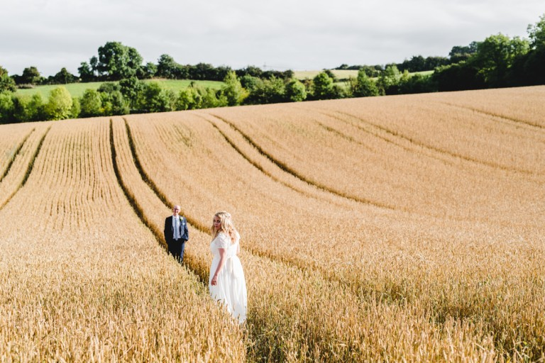 Upcote Barn wedding couple posing in a field for photographs