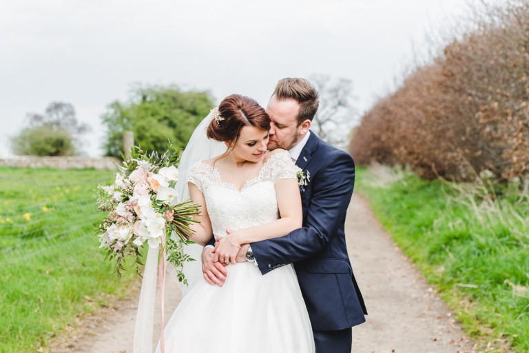 A groom and a bride at the great tythe abrn in Tetbury