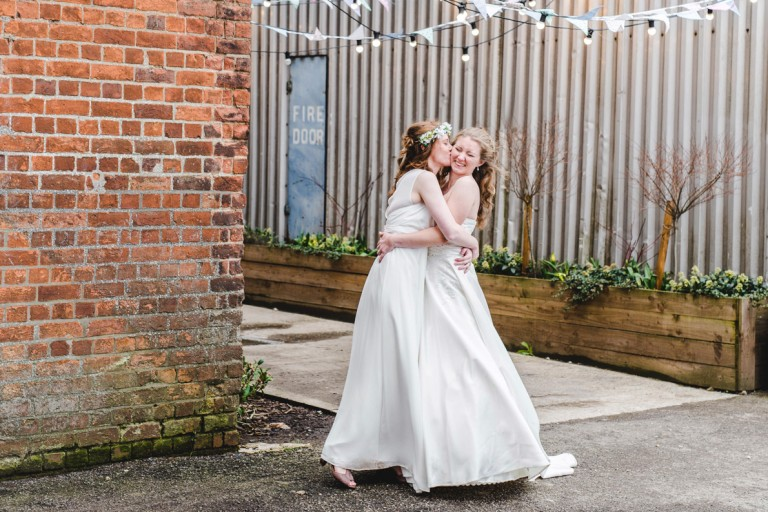 Two brides hugging at their Gloucestershire Brewery Wedding