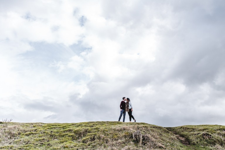 A couple standing on a hill photographed from below