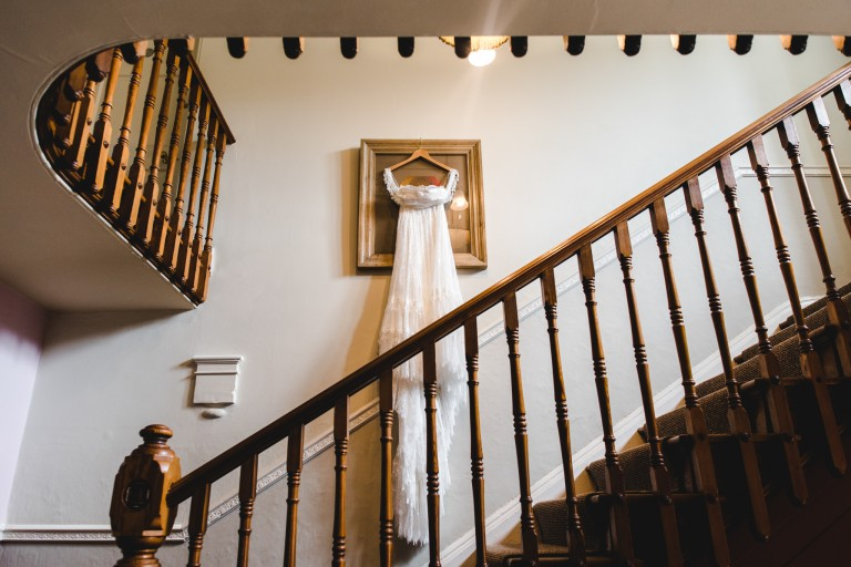 brides dress hanging from a picture frame
