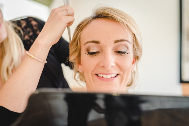 A close up of a bride having her hair styled before her wedding