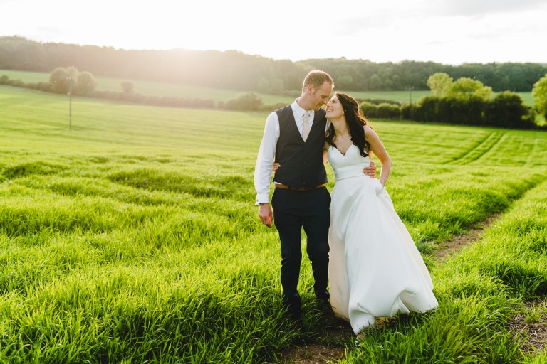 A couple at their upcote barn wedding in a field
