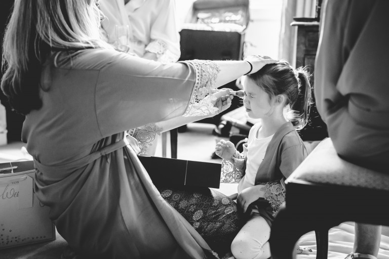 A flower girl having her hair styled for a wedding
