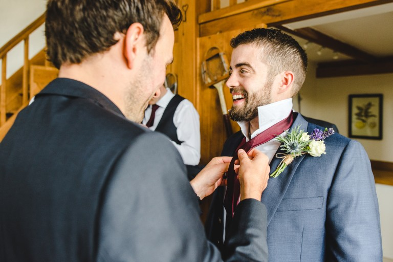 Agroomsman attaching the groom's buttonhole at a Merriscourt wedding