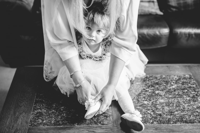 A black and white picture of a girl at a wedding having her shoes put on