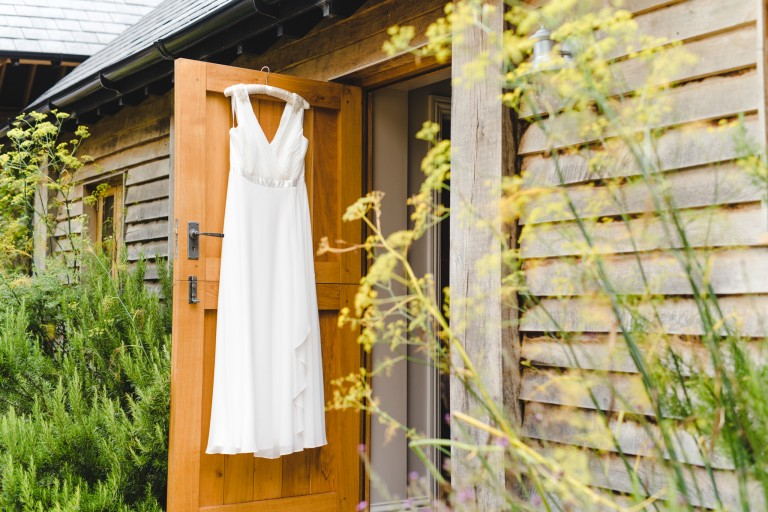 A wedding dress hanging on the door of the bridal suite at Upcote