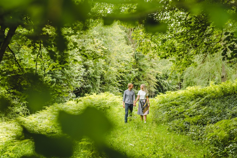 An engaged couple walking in woodland