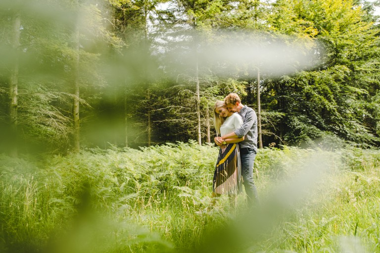 An engaged couple standing in the woods